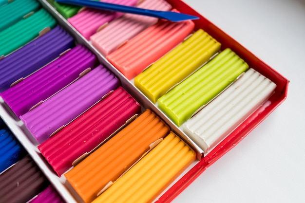 Kolorowa plastelina dziecięca na białej powierzchni, kolorowa glina do modelowania ciasta, wielokolorowe brykiety z miękkiej plasteliny do modelowania z miękkim skupieniem. plastikowy kolorowy materiał do edukacji artystycznej dzieci.