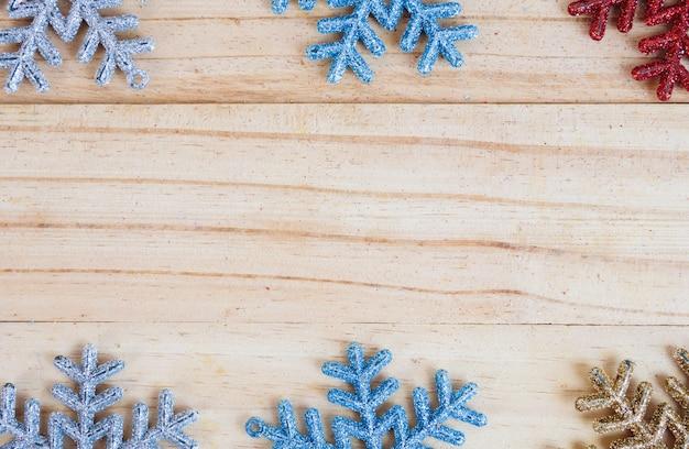 Kolorowa płatek śniegu rama na starym drewnianym tle z pustym