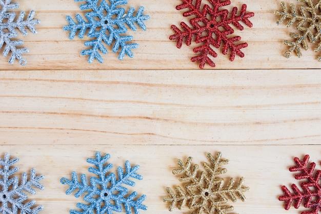 Kolorowa płatek śniegu rama na starym drewnianym tle