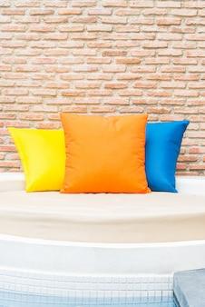 Kolorowa poduszka na łóżku przy hotelowym kurortu pływackim basenem