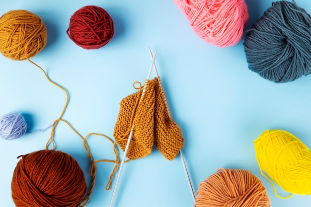 Kolorowa przędza na drutach, niebieskie tło. projekt dziewiarski w toku. widok z góry
