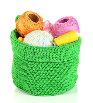 Kolorowa przędza na drutach w zielonym koszu na białym tle