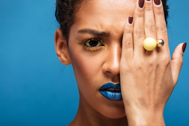 Kolorowa przestraszona lub obrażona kobieta mieszanej rasy z modnym makijażem i akcesoriami zakrywającymi oko ręką, na niebieskiej ścianie