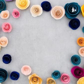 Kolorowa rama z papierowymi kwiatami na cementowym tle