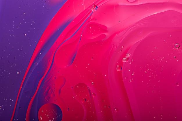 Kolorowa różowo-fioletowa tekstura w postaci rozmazów i kropli oleju na powierzchni wody, tło gradientowe
