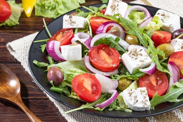 Kolorowa sałatka grecka z pomidorkami koktajlowymi, oliwkami, cebulą i białym serem na stole