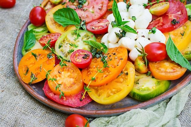 Kolorowa sałatka pomidorowa z mozzarellą serową i bazylią. sałatka caprese. wegańskie jedzenie.