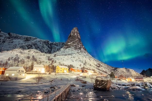 Kolorowa skandynawska wioska z zorzą polarną nad szczytem góry na lofotach