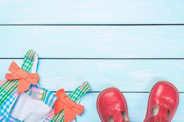 Kolorowa sukienka i czerwone buty na jasnoniebieskiej drewnianej pastelowej powierzchni.