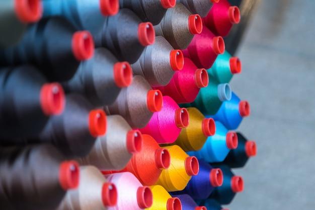 Kolorowa szpula nici do haftu stosowana w przemyśle odzieżowym, rząd wielokolorowych rolek przędzy, sprzedaż materiałów do szycia na rynku