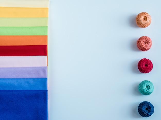 Kolorowa tęcza przędzy na drutach. haczyki, nożyczki i igły dziewiarskie