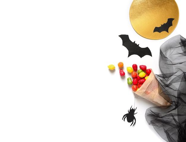 Kolorowa uczta w papierowej torbie na białym tle. koncepcja wakacje halloween. skopiuj miejsce.