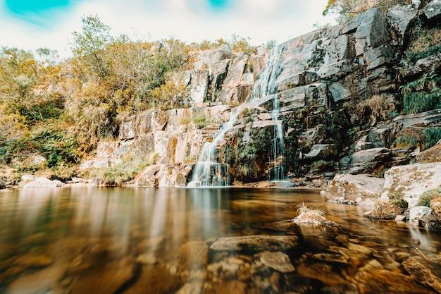 Kolorowa woda spada w środku lasu w słoneczny dzień