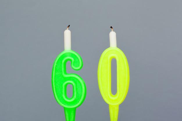 Kolorowa woskowa urodzinowa świeczka na szarym tle