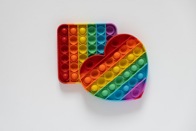 Kolorowa zabawka antystresowa pop it dla dzieci. tęcza w kształcie serca na białym tle. 2 zabawki - kwadratowe iw kształcie serca. pop to zabawka.