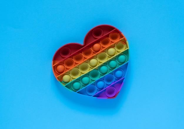 Kolorowa zabawka antystresowa pop it dla dzieci. tęcza w kształcie serca na białym tle na niebieskim tle.
