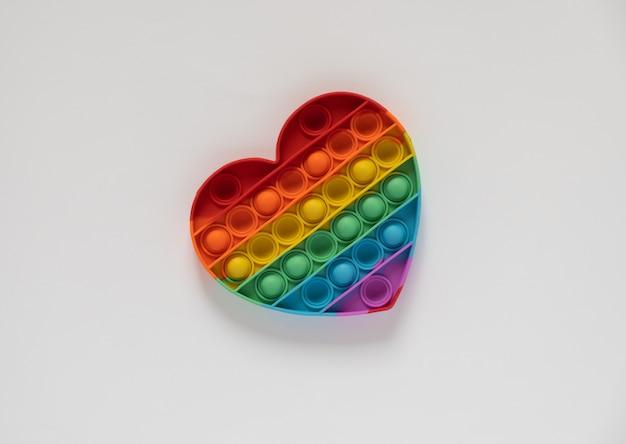 Kolorowa zabawka antystresowa pop it dla dzieci. tęcza w kształcie serca na białym tle. pop to zabawka.