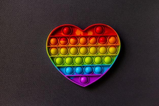 Kolorowa zabawka sensoryczna fidget push pop to serce na czarnym tle