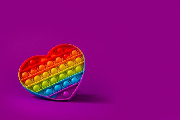 Kolorowa zabawka sensoryczna fidget push pop to serce na fioletowym tle