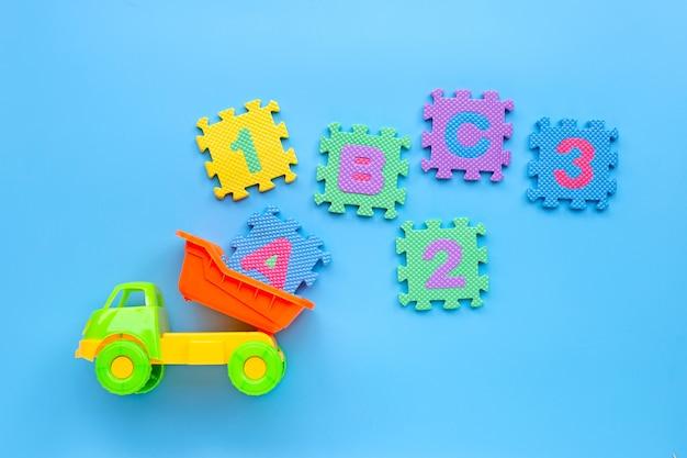 Kolorowa zabawka z angielskim alfabetem i liczebnikami na błękitnym tle. koncepcja edukacji