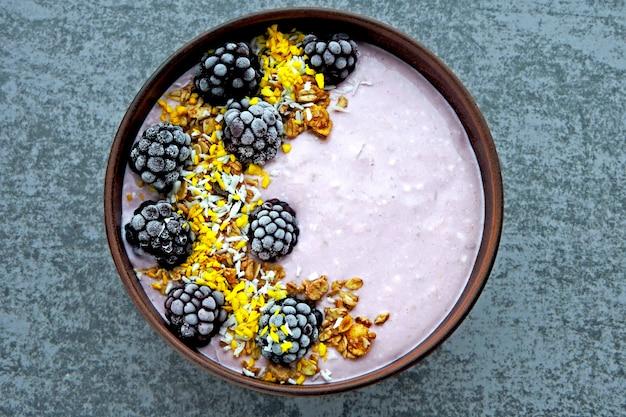 Kolorowa zdrowa śniadaniowa miska z różowym jogurtem i jeżynami.