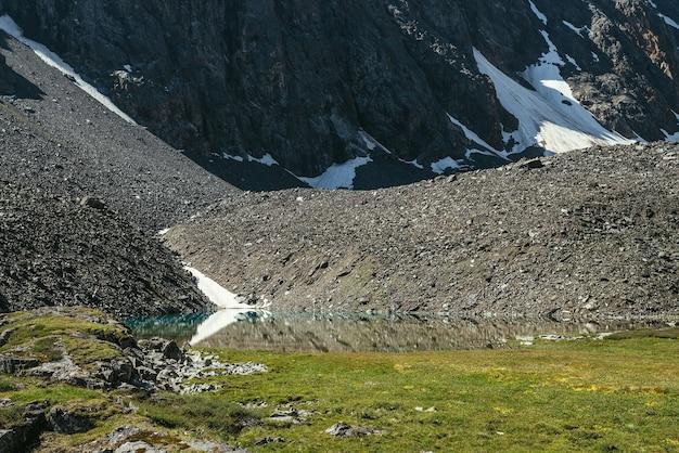 Kolorowa zielona sceneria z górskim jeziorem w pobliżu kamienistej góry ze śniegiem. piękny malowniczy krajobraz z czystą taflą wody górskiego jeziora. lazurowe jezioro polodowcowe w słońcu. turkusowe jezioro lodowcowe.