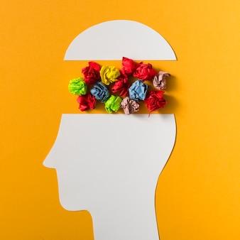 Kolorowa zmięta papierowa piłka wśrodku papierowego cięcia głowy na żółtym tle