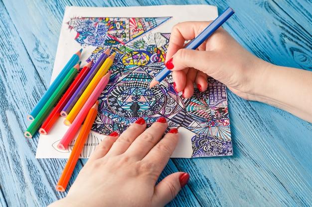 Kolorowanki dla dorosłych kolorowe kredki przeciwstresowe. hobby rąk kobiety maluje malarz odprężający