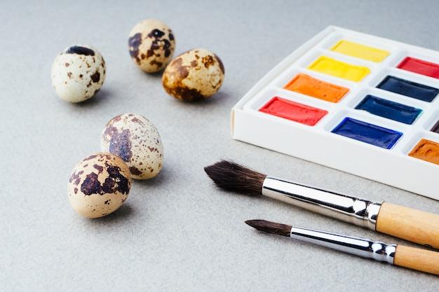 Kolorowanki na wielkanoc. farby, pędzle, jajka przepiórcze na szarym tle. przygotowanie do obchodów wielkanocy, tradycyjne dekoracje, tło. kreatywna koncepcja.
