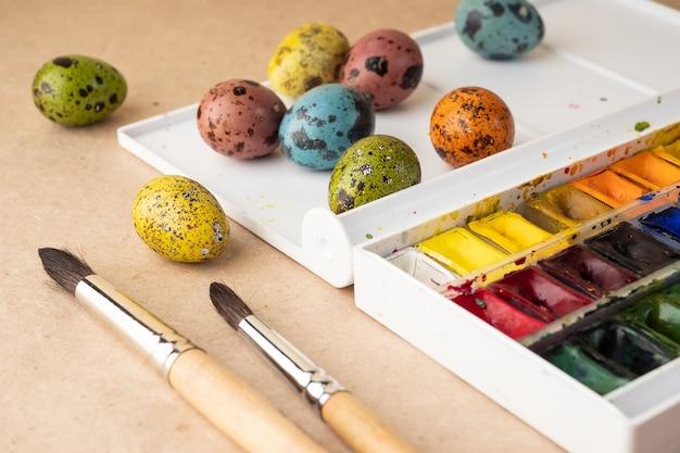 Kolorowanki na wielkanoc. farby, pędzle, przepiórcze jajka na tle rzemieślniczym. przygotowanie do obchodów wielkanocy, dekoracje na święta, tło. kreatywna koncepcja.
