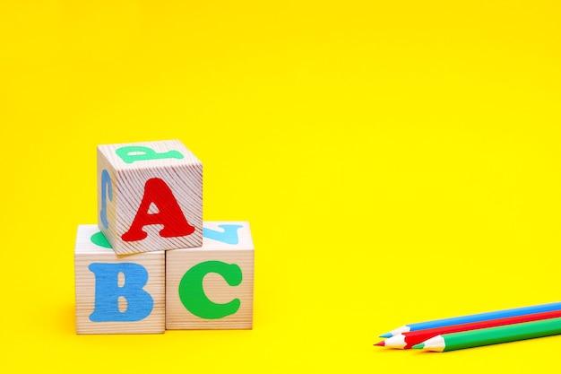 Kolorowe abc na drewnianych kostkach i kolorowe ołówki na żółtym tle