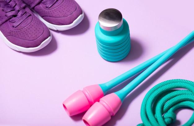 Kolorowe akcesoria do gimnastyki artystycznej. zielona lina, niebieskie kluby do rytmicznej gimnastyki, niebieska butelka na wodę i liliowe trampki na jasnym tle