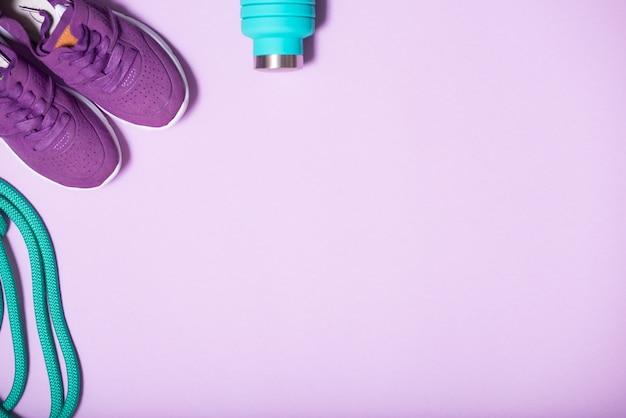 Kolorowe akcesoria do gimnastyki rytmicznej, fitness, biegania. zielona skakanka, niebieska butelka wody i liliowe trampki na jasnym tle z miejsca kopiowania