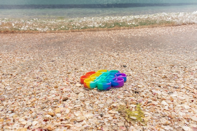 Kolorowe antystresowe sensoryczne pop to zabawka na piasku z wodą na plaży. koncepcja lato i relaks. autyzm potrzebuje silikonowej zabawki antystresowej