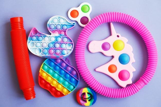 Kolorowe antystresowe zabawki sensoryczne fidget na niebieskim tle