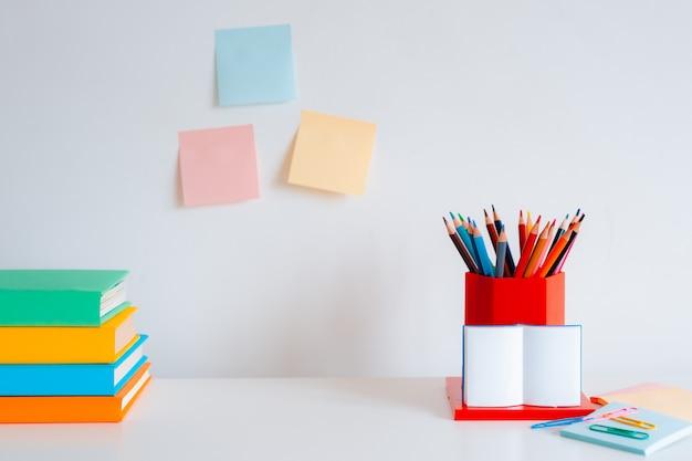 Kolorowe artykuły papiernicze, kolorowe kredki i jasne książki na białej ścianie.