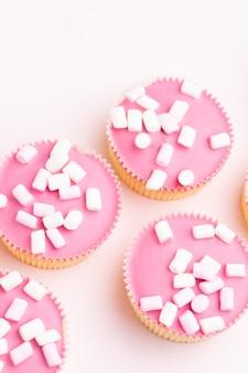 Kolorowe babeczki na różowym tle