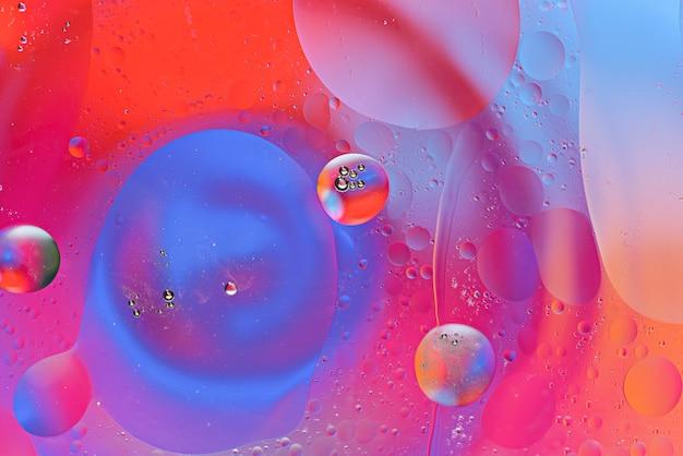 Kolorowe bąbelki i rozmazane krople oleju na powierzchni wody na kolorowym tle, tekstura sztuka