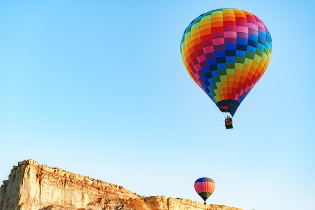 Kolorowe balony latające na czystym niebie w pobliżu ogromnej białej góry