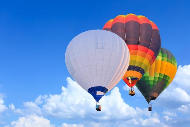 Kolorowe balony na ogrzane powietrze w locie nad błękitnym niebem