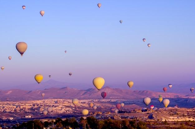 Kolorowe balony o świcie uderzają w dolinę.