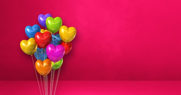 Kolorowe balony w kształcie serca kilka na tle różowej ściany. renderowanie 3d