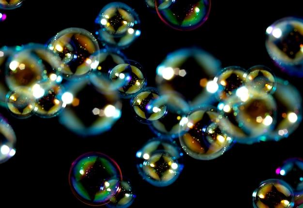 Kolorowe bańki mydlane unoszą się na ciemnym tle.