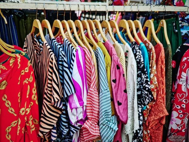 Kolorowe bluzki dla pań wiszące na stojaku do sprzedaży w sklepie odzieżowym