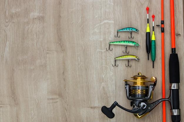 Kolorowe błystki przynęty wędkarskie bajty pływają kołowrotek i pomarańczowa wędka na drewnie miejsce na tekst