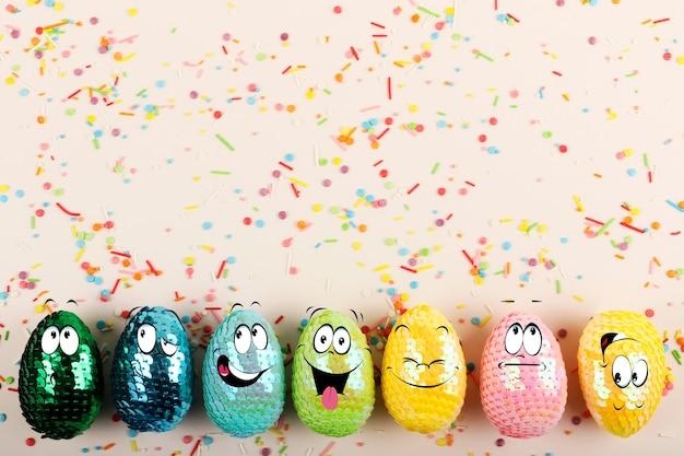 Kolorowe błyszczące pisanki z cekinów z zabawnymi buziami żywe ciasto na pastelowym tle