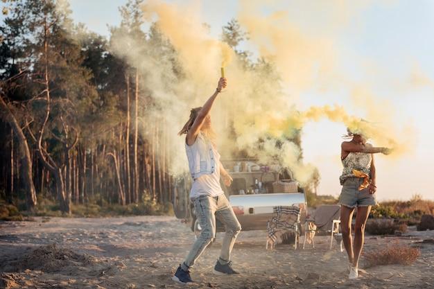 Kolorowe bomby ogniowe. para aktywnych młodych podróżników mieszkających w przyczepach stacjonarnych trzymających kolorowe bomby ogniowe