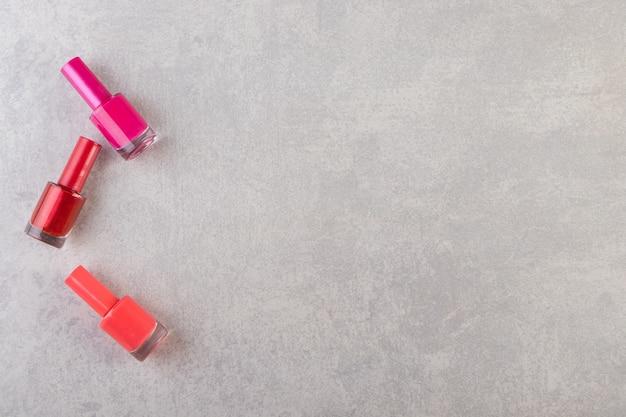 Kolorowe butelki z lakierem do paznokci ustawione na kamiennym stole.