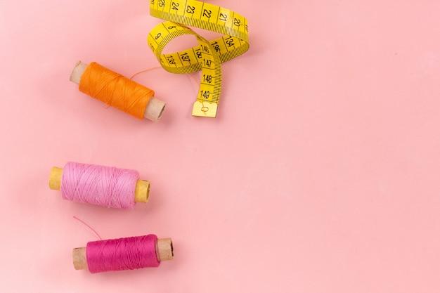 Kolorowe cewki nici na różowym tle z copyspace, szycie.