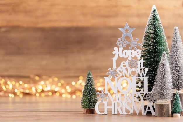 Kolorowe choinki na tle bokeh drewniane,. koncepcja obchodów świąt bożego narodzenia. kartka z życzeniami.